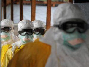 Funcionários da área da saúde usam roupas de proteção contra o ebola em hospital