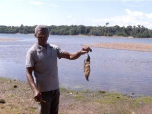 Pescador mostra carcaça de peixe (Foto: TV Anhanguera)